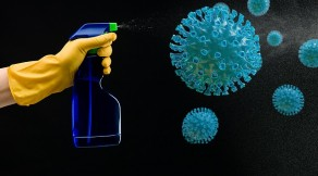 hand with rubber glove holding cleaning bottle and spraying liquid, on black background